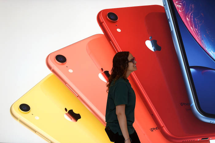 Seorang wanita sedang berjalan di depan poster iPhone XR