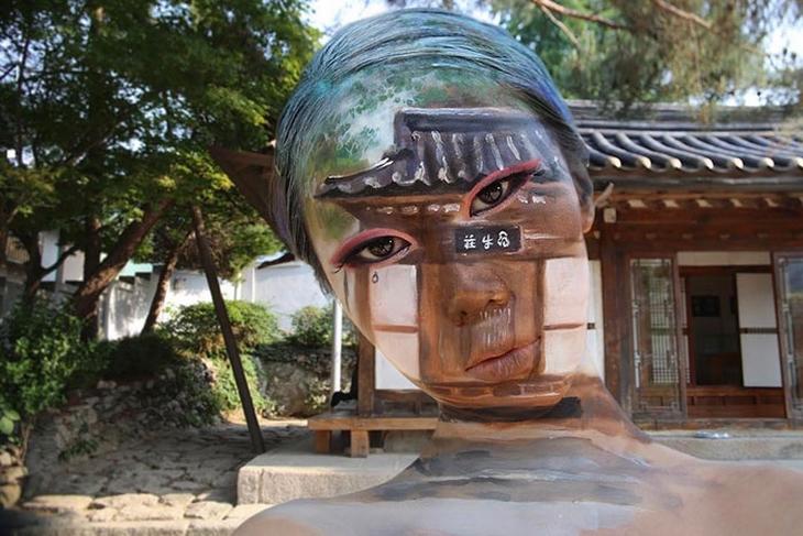 Kwikku, Wajah hingga lehernya dilukis seperti objek rumah yang ada dibelakangnya Layaknya bunglon yang pandai beradaptasi terhadap lingkungan